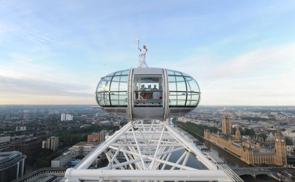 Pic: A spectacular view! Amelia Hempleman-Adams holds the Olympic Flame on top of the London Eye #London2012TorchRelay <a href=