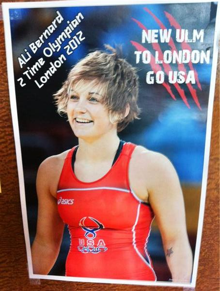 In New Ulm, Minn. you can find posters of local Olympian Ali Bernard displayed in many a store window.  This one is at the counter of Lola's Larkspur market.<br />