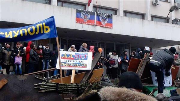 Demonstranter utanför borgmästarens kontor i staden Mariupol, drygt 30 mil söder om Slovjansk. Enligt uppgifter från Reuters ska byggnaden ha ockuperats. Foto: TT