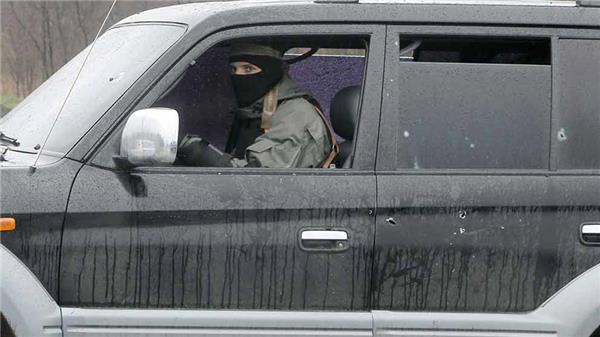 En pro-rysk aktivist kör iväg i en bil som skottskadats under eldstriderna utanför Slovjansk. Foto: TT/AFP