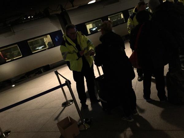 Kontrollanterna fotograferar resenärernas ID-kort. Nu går det undan eftersom det står ett tåg på perrongen och är klart för avfärd.
