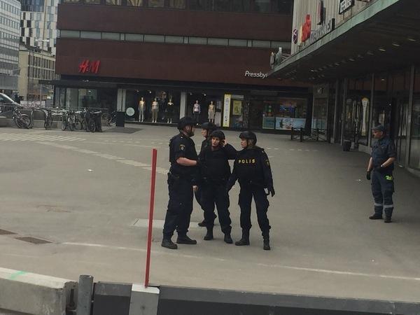 Poliser samlade innanför avspärrningarna.