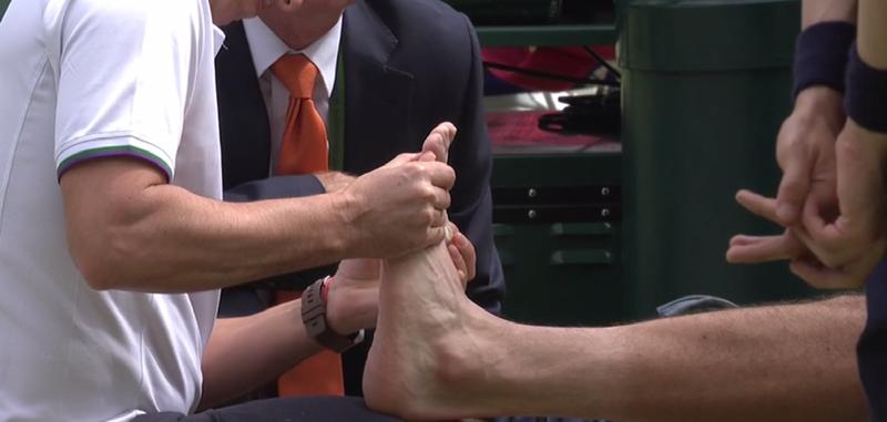 El fisioterapeuta trabajando el pie izquierdo de Marin Cilic