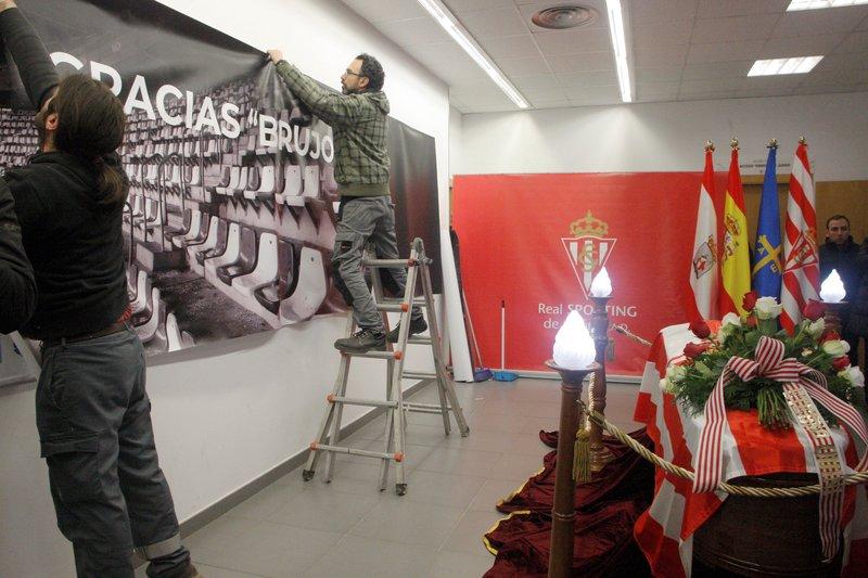 Operarios del Sporting colocan una pancarta de agradecimiento a Quini al lado de su féretro
