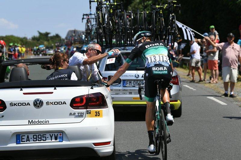 MARCUS BURGHARDT (Bora), asistido por el coche médico del Tour de Francia tras caerse en la zona neutralizada de la etapa