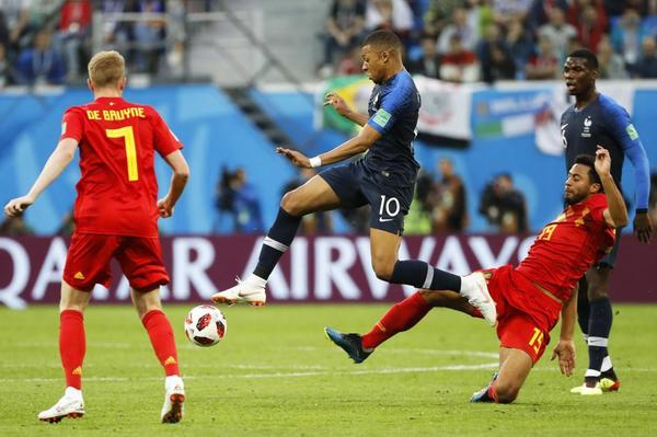 Kylian Mbappe ante el jugador belga Moussa Dembele