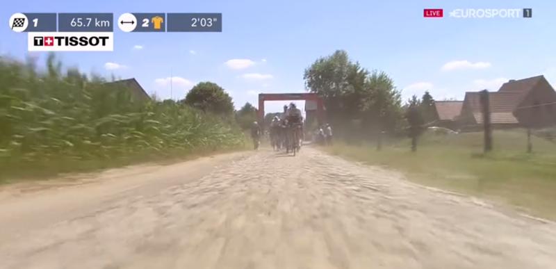 La polvareda es notable cuando los ciclistas atraviesan un tramo adoquinado