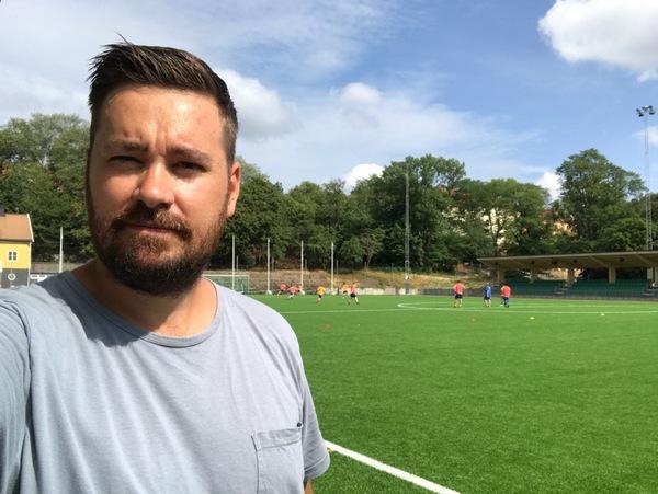 Reporter Kristofer Carlsson finns på plats i Stockholm för att rapportera från U21 EM i fotboll.  I bakgrunden tränar det svenska laget inför den första EM-matchen mot Grekland, som spelas på onsdag klockan 18:00 på Hammarby IP.