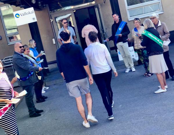 Valarbetare lockar med sina valsedlar när kungsholmsborna anländer till vallokalen i Eiraskolan. Foto: Stefan Bokström, SVT