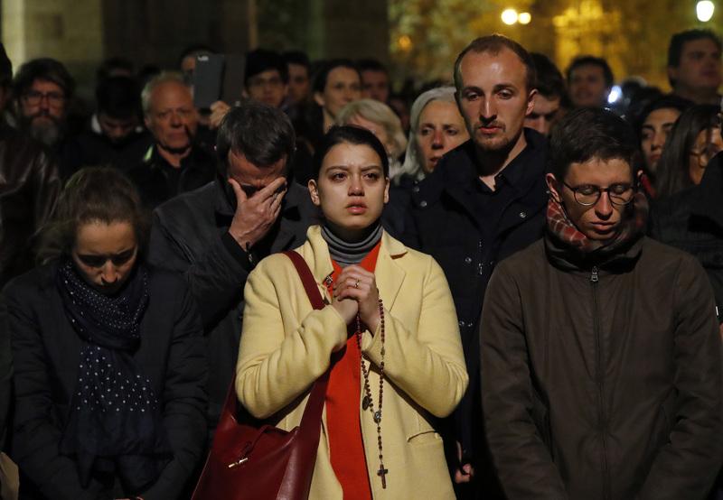 Pese a que ya está entrada la noche en París, multitud de personas aún se encuentran rezando por Notre Dame