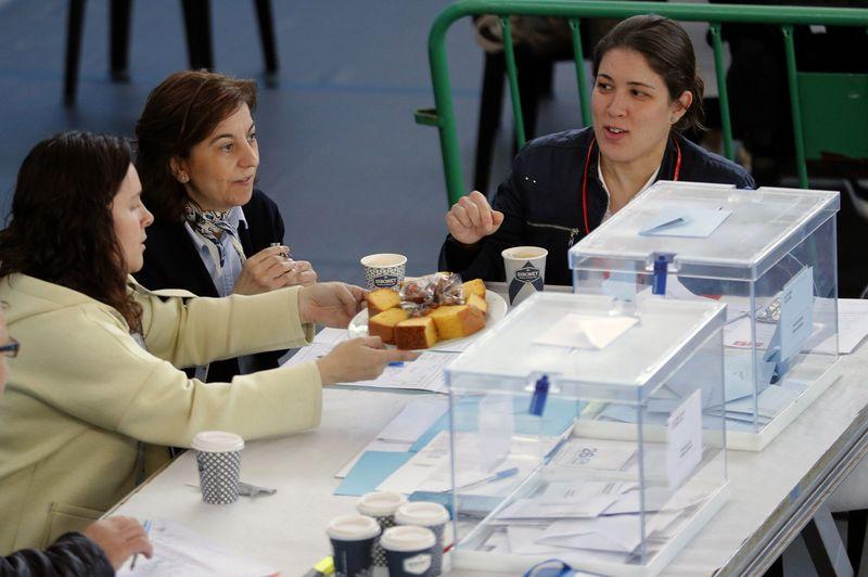 Los miembros de una mesa toman un café esta mañana durante la jornada electoral en un pabellón polideportivo en Ames, A Coruña. EFE/Lavandeira jr