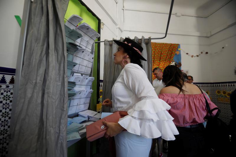 Feria y elecciones. En la imagen, dos mujeres vestidas de flamenca eligen sus papeletas en un colegio de Córdoba donde se está celebrado la Feria de Nuestra Señora de la Salud. EFE/Salas