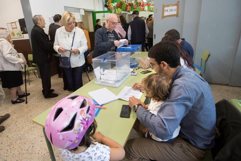 Un vocal de una de las mesas del colegio Ausías March de Barcelona realiza su trabajo mientras cuida de sus hijos, en las elecciones municipales y europeas que se celebran este domingo. EFE/Marta Pérez