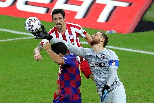 Oblak, en el momento en el que ha metido el puño para evitar el remate de Luis Suárez