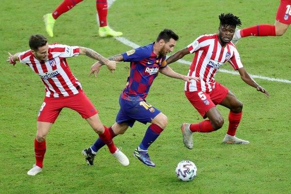 Messi intentando irse de los defensas del Atlético