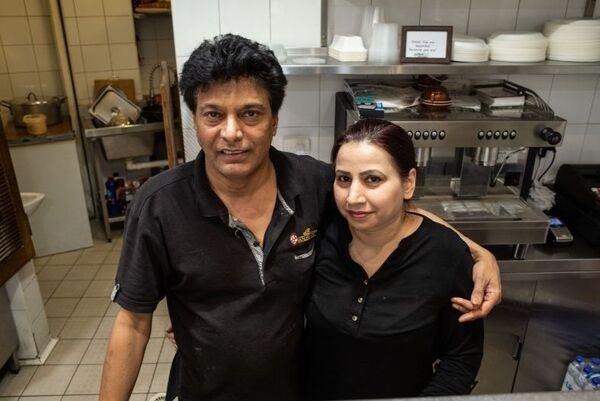 A couple standing in a restaurant kitchen.