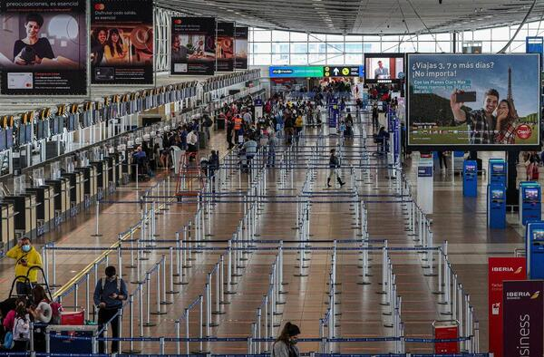 An airport in Santiago is seen with relatively few travellers near check-in desks.