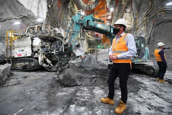 Daniel Andrews, dressed in a hard hat and high-vis, stands in front of heavy machinery on a construction site.
