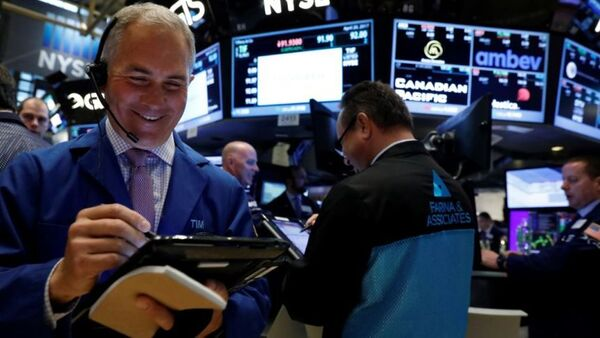 Traders work on the floor of the New York Stock Exchange, with one man seen in the front left writing on a screen and smiling. A headset sits atop his head.