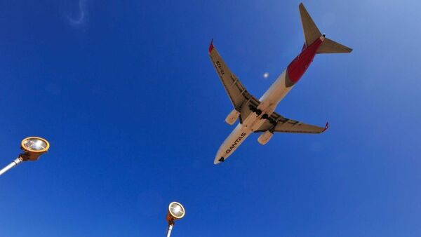 The white, red and silver underside of a Qantas plane is seen flying over a clear blue sky in Adelaide.