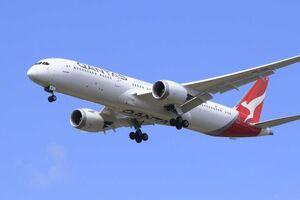 A Qantas plane flys against a blue sky
