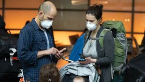 A man and a woman stand looking at a phone wearing backpacks and facemasks