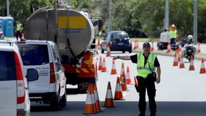 A police officer directs traffic through a line of cones