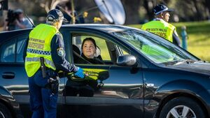 A woman in a car is spoken to by police in yellow fluro vests