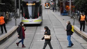 People walk in front of a tram in Melbourne