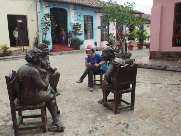 A woman in a pink hat sits among three statues of people also sitting down in a street square with yellow, pink and blue buildings behind them.