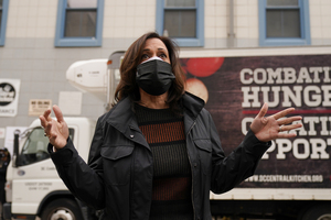 Vice President-elect Kamala Harris answers a question from the media while wearing a mask.
