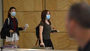 Two women walk wearing facemasks