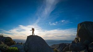 A silhouette of a man with hiking equipment stands on top of a rock