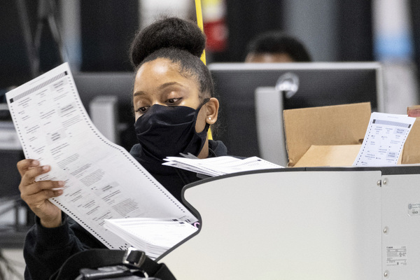 worker in a mask scans ballots as the presidential recount process gets under way in Georgia
