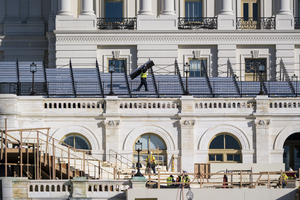 construction crews work on the platforms where the president-elect will take the oath of office, at the Capitol in Washington