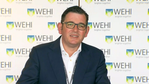 Daniel Andrews smiles in front of a white background with WEHI written on it.