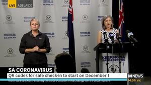 Professor Spurrier stands at a podium next to a female AUSLAN interpreter.