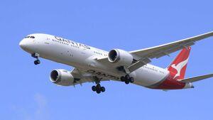 A Qantas jet flies in blue skies