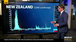 Casey Briggs stands in front of a curve of New Zealand's cases