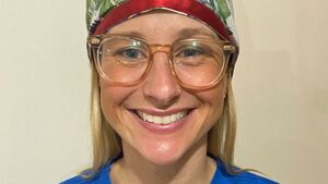 A woman wearing glasses and a head covering smiles at the camera