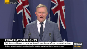 Anthony Albanese stands in front of two Australian flags