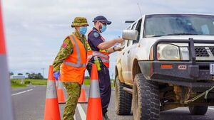 A police officer and a member of the army check a ute