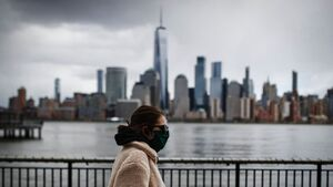 A masked woman walks past the New York skyline