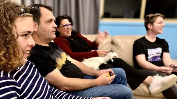 A family sits on a couch playing video games