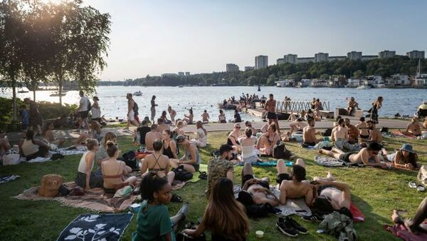 A crowd of young people in beach attire sit near a river on a sunny day in Sweden.