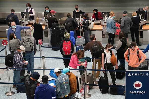 People line up at an airport check-in line at a US airport before Thanksgiving 2020