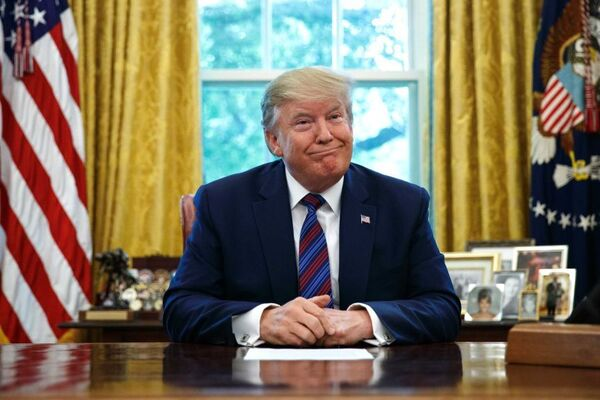 Donald Trump smiles as he sits behind the Resolute Desk in the White House