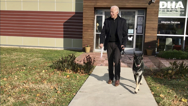 Joe Biden walks out of a building with his newly-adopted dog Major
