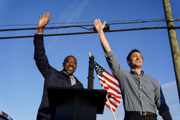 Georgia Democratic candidates for U.S. Senate Raphael Warnock, left, and Jon Ossoff, right, gesture toward a crowd during a campaign rally
