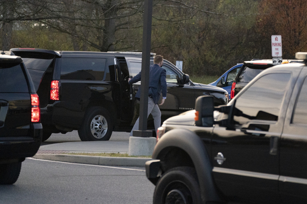 A person gets out of a black 4WD in Joe Biden's motorcade